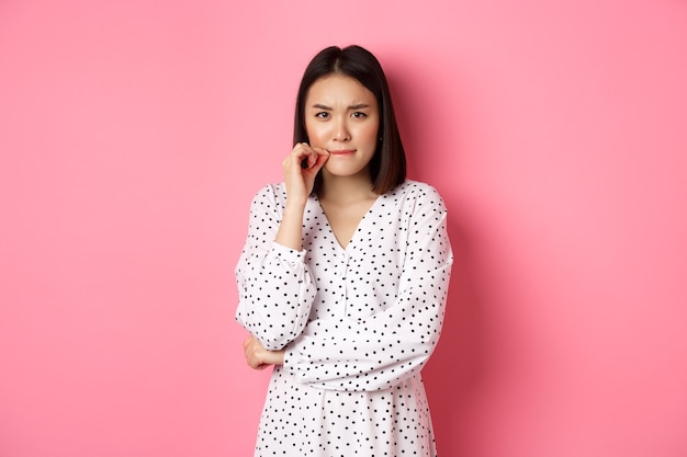 Brunette asian woman in dress looking displeased, frowning and zipping mouth, seal lips with promise, standing over pink background.