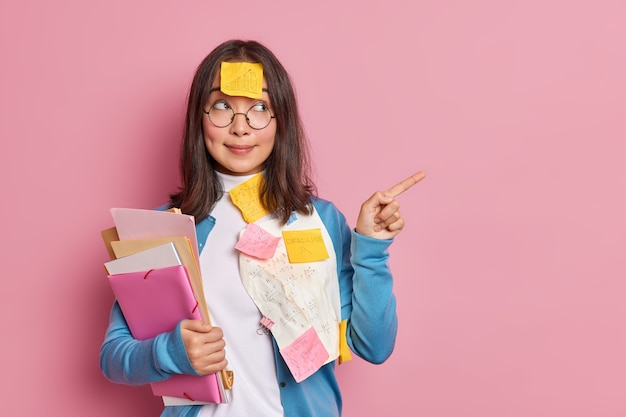 Brunette asian woman manager examines paper documents points away on blank space works on startup project.