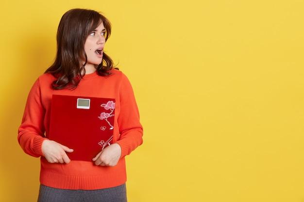 갈색 머리 운동 여자 규모를 잡고 얼굴에 놀람을 표현, 옆으로 열린 입, 노란색 위에 포즈 모델, 광고 복사 공간.