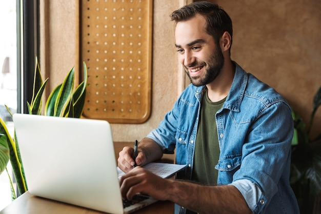 Brunette bearded man wearing denim shirt writing and typing on laptop while working in cafe indoors