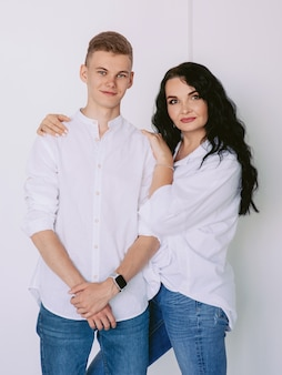 白いシャツとジーンズの十代の息子とブルネットの美しいスタイリッシュな女性