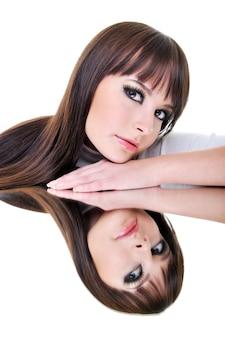 ブルネットの美しい女性は鏡で反射に直面します