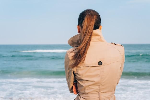 Brunette in beige coat looks on the sea