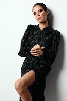 ブルネットの黒いドレスファッショングラマー孤立した背景