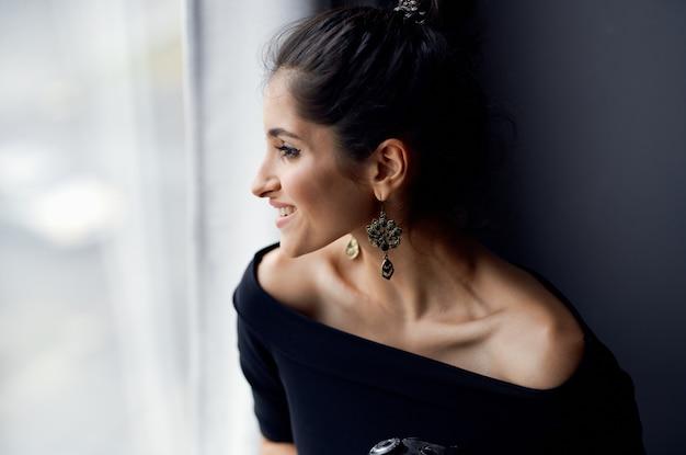 Brunette in a black dress near the window posing lifestyle studio