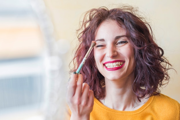 Brunette blogger doing her make up