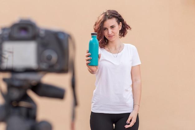 Брюнетка блоггер пьет воду из бутылки