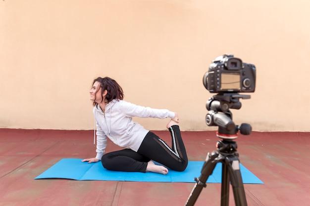 Брюнетка-блоггер записывает занятия йогой