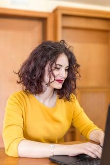 Brunette blogger writing on the laptop