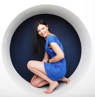 Brunette in blue dress sitting in a circle