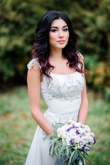 Brunette bride holds wedding bouquet with greenery posing outside