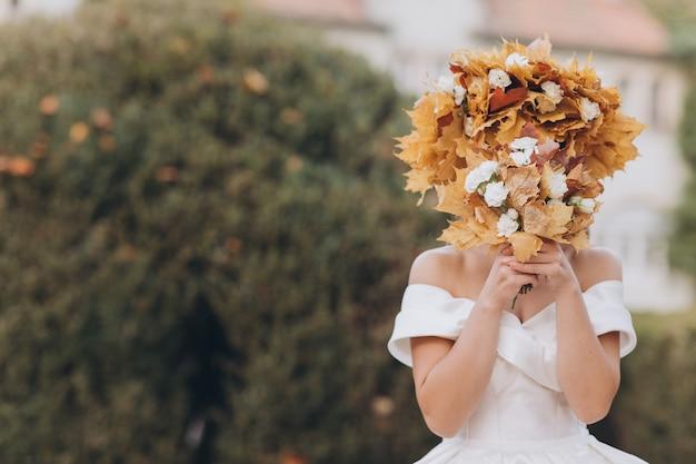 葉の花輪の白いドレスを着た秋の森のブルネットの花嫁。