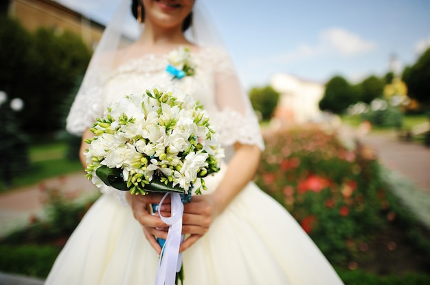 花の近くの花束とブルネットの花嫁