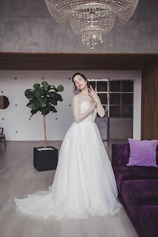 고급스러운 인테리어의 웨딩 드레스에 화장과 갈색 머리 신부