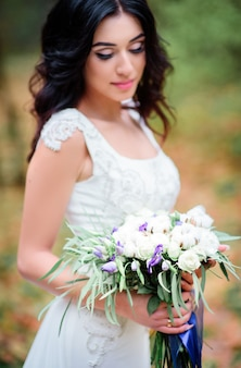 Brunette bride with tender pink lips holds wedding bouquet made of cotton and white roses
