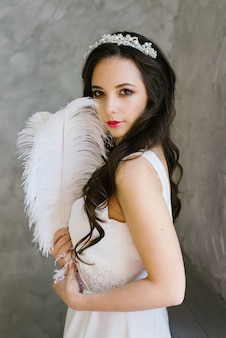 Brunette bride with tiara and professional makeup holding a white ostrich feather