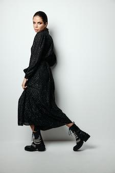 ブルネットの明るいメイクの黒いドレスの魅力的なモデル