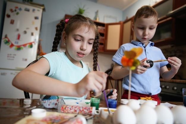 갈색 머리 형제와 자매는 부엌에서 집에서 테이블에 앉아 부활절 달걀을 장식