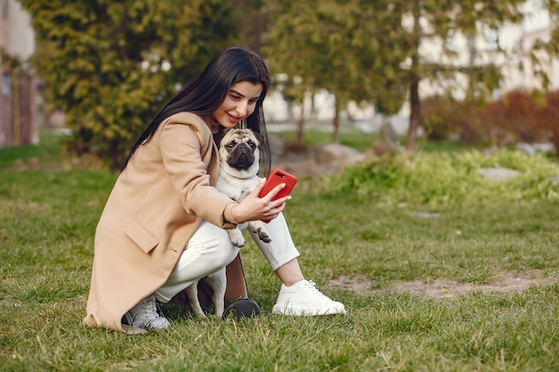 Bruna in un cappotto marrone cammina con pug