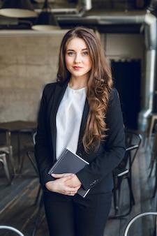 ウェーブのかかった長い髪と青い目をしたブルネットのビジネス女性は手でノートを保持しています。