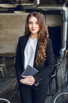 Brunette business woman with wavy long hair and blue eyes stands holding a notebook in hands