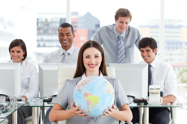 Brunette businesswoman and her team showing a terrestrial globe
