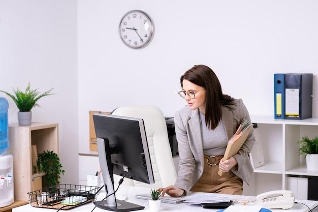 Брюнетка-бизнесвумен в куртке, стоящая за столом и выключающая компьютер, покидая офис