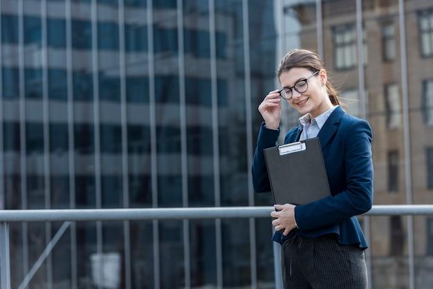 Brunette businesswoman posing outdoors
