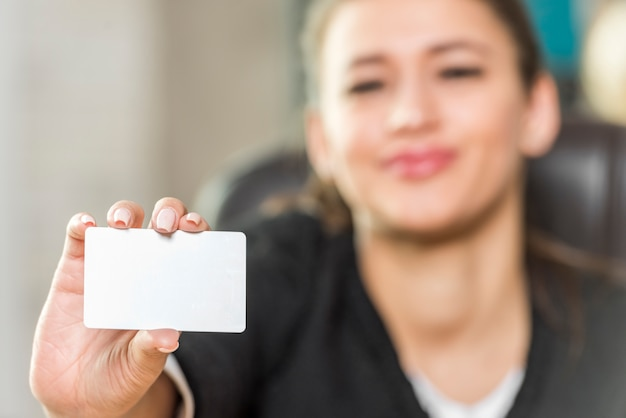 Brunette businesswoman showing card
