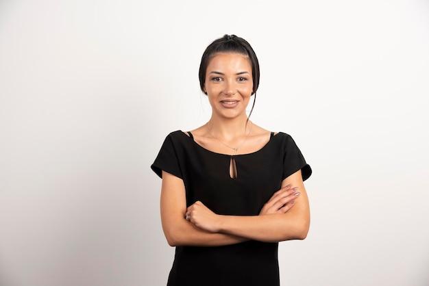 Brunette businesswoman standing on white wall.