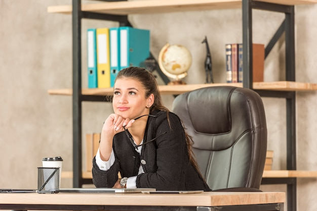 Brunette businesswoman thinking at her office