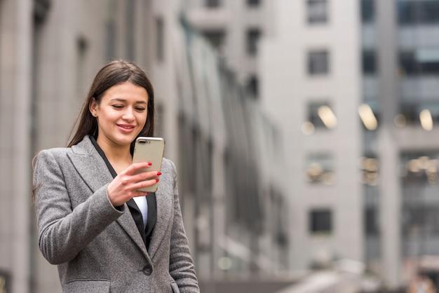 Brunette businesswoman using her smartphone