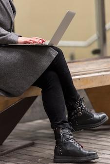 Brunette businesswoman using laptop outdoors