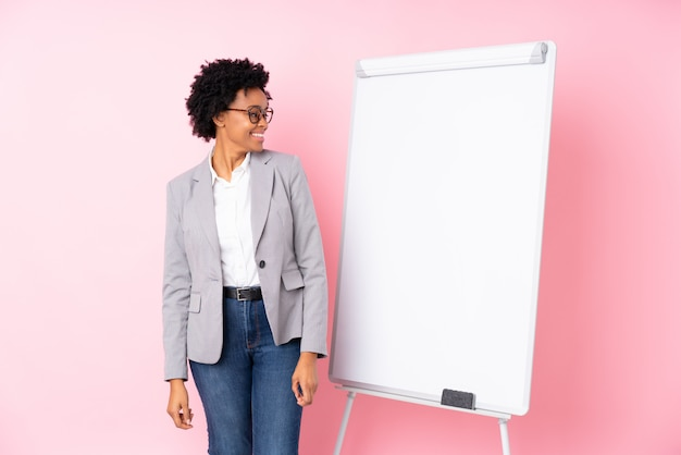 Brunette businesswoman with whiteboard over isolated pink background