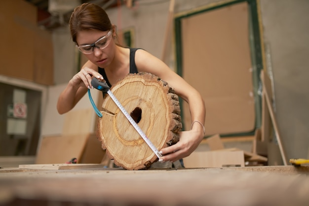 Brunette carpenter in glasses with tape measure and saw cut tree in her hands in workshop