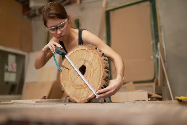 안경을 쓴 갈색 머리 목수, 줄자가 있는 안경을 쓰고 작업장에서 손에 잘린 나무를 보았다
