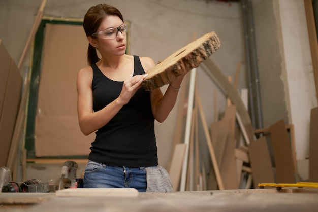 Brunette carpenter with saw cut tree in hands in workshop