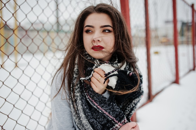 Brunette casual girl in scarf at winter on street.
