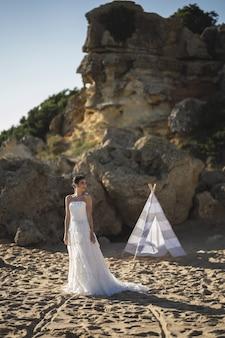 Bruna sposa caucasica in posa sulla spiaggia davanti a una tenda bianca