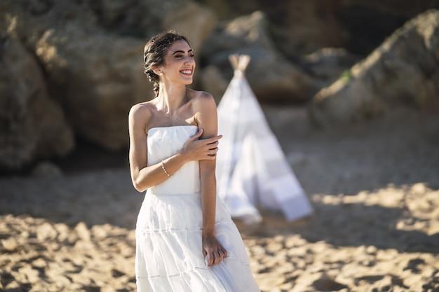 해변에서 포즈를 취하는 동안 웃 고 갈색 머리 백인 신부