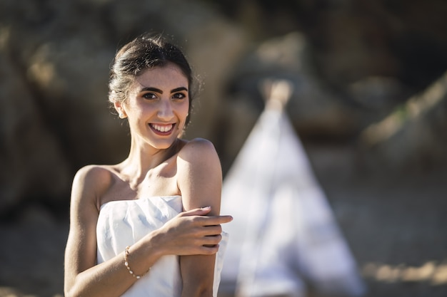 ビーチでポーズをとって笑っているブルネットの白人花嫁