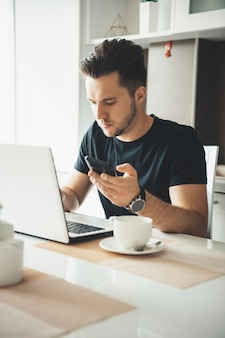 Brunette caucasian businessman with bristle working from home at the laptop and chatting on mobile
