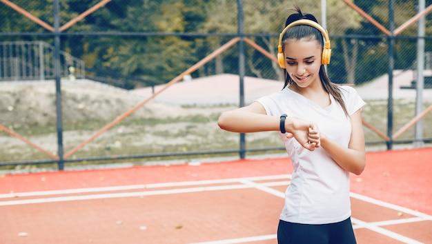 Брюнетка кавказская девушка фиксирует время на своих умных часах после утренней зарядки в наушниках