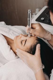 Брюнетка кавказская дама ждет, чтобы закончить процедуру чистки лица во время сеанса спа