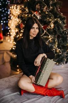 그녀의 얼굴에 호기심이 표정으로 검은 색의 갈색 머리 매력적인 여자는 침대에 앉아 선물 상자를 열 준비