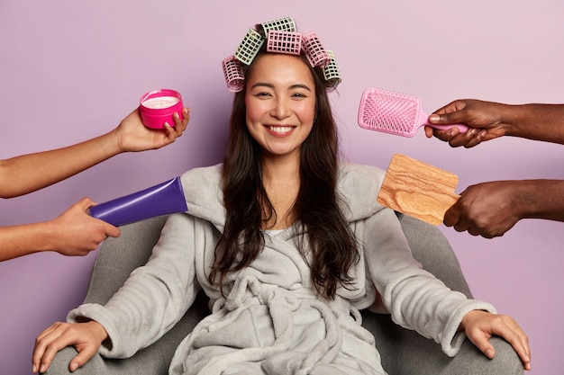 Brunette cheerful woman makes curly hair with curlers, wears soft bathrobe