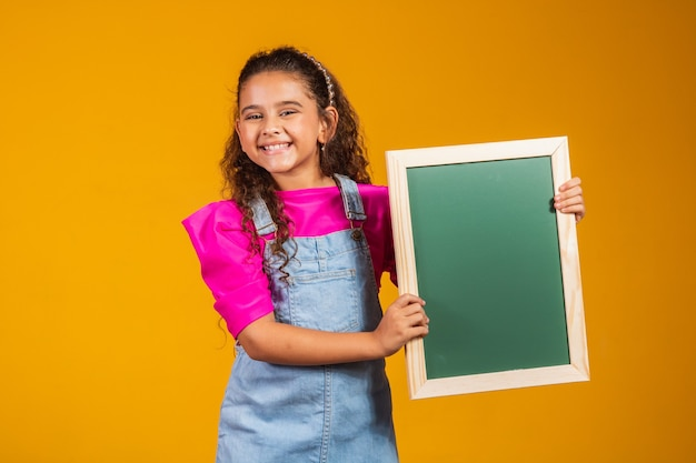 黄色の背景に黒板を保持しているブルネットの子供。