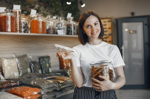 ブルネットは食べ物を選びます。シナモンの瓶を持っている女性。スーパーマーケットで白いシャツを着た女の子。
