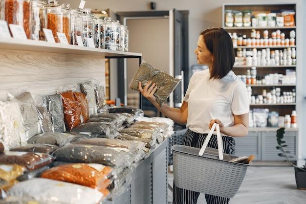 갈색 머리는 음식을 선택합니다. 여자는 쇼핑 카트를 들고있다. 슈퍼마켓에서 흰색 셔츠에있는 소녀.