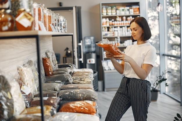 ブルネットは食べ物を選びます。女性はドライフルーツを持っています。スーパーマーケットで白いシャツを着た女の子。
